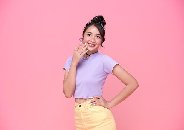 Feliz jovem adolescente asiática na parede rosa.