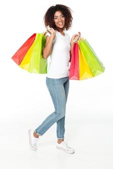 Feliz jovem africana segurando sacolas de compras.