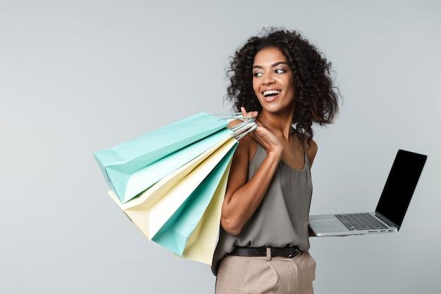 Feliz jovem africana vestida de maneira casual, isolada, segurando um laptop, carregando sacolas de compras