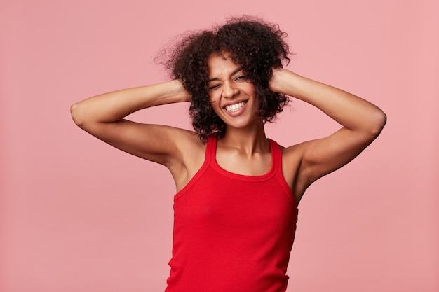 Feliz, jovem afro-americana gosta de dançar, piscar, aproveitar o tempo de descanso, sorri animadamente, toca seu cabelo afro encaracolado, leva as mãos à cabeça, se diverte, vestindo camiseta vermelha, isolada no rosa