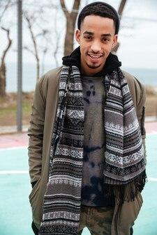 Feliz jovem afro-americano em pé ao ar livre