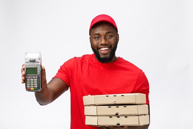 Feliz jovem afro-americano entregador segurando uma máquina de pagamento com cartão eletrônico e um produto de entrega.