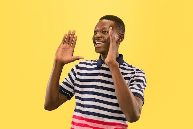 Feliz jovem afro-americano isolado no fundo amarelo do estúdio, expressão facial. belo retrato masculino de meio comprimento. conceito de emoções humanas, expressão facial.