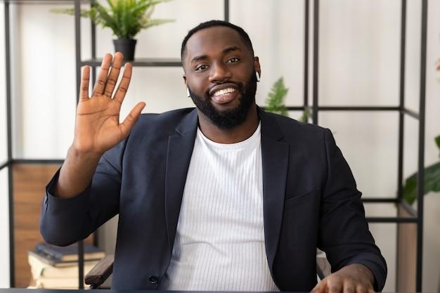 Feliz jovem afro-americano participa de negociações virtuais distantes por meio de teleconferência. conceito de videochamada