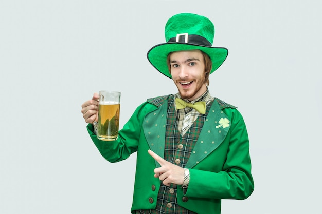 Feliz jovem alegre em verde saint patick terno segurando a caneca de cerveja e olhar. ele aponta e sorri. isolado em cinza.