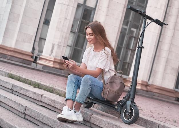 Feliz jovem aluna sentada em uma scooter