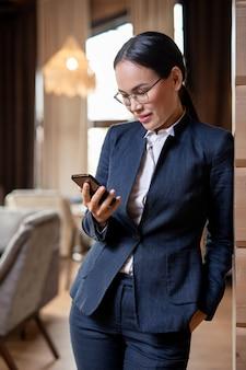 Feliz jovem asiática em um terno elegante lendo mensagem ou rolando em um smartphone em um restaurante luxuoso