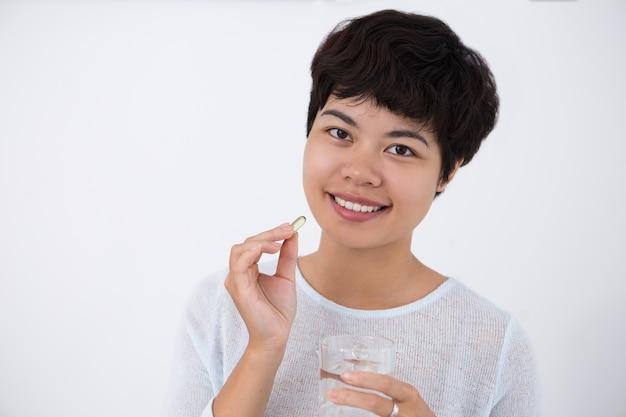 Feliz, jovem, asiática, mulher, tomando, pílula