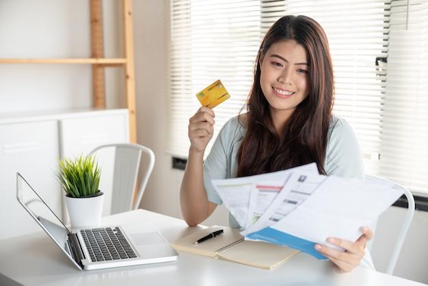 Feliz jovem asiática sorrindo segurando tantas contas de despesas