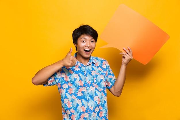 Feliz jovem asiático em pé isolado sobre o espaço amarelo, segurando o balão.