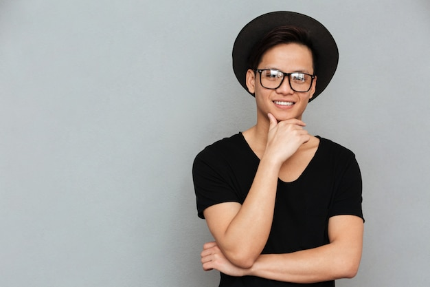 Feliz jovem asiático em pé isolado sobre parede cinza
