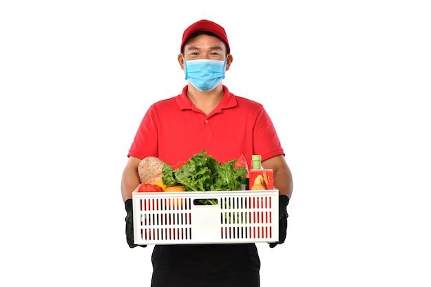 Feliz jovem asiático entregador de uniforme vermelho, máscara médica e carregando uma caixa de supermercado nas mãos, isoladas no fundo branco