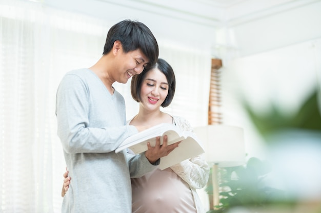 Feliz, jovem, asiático, homem, e, bonito, mulher grávida, livro de leitura em casa.