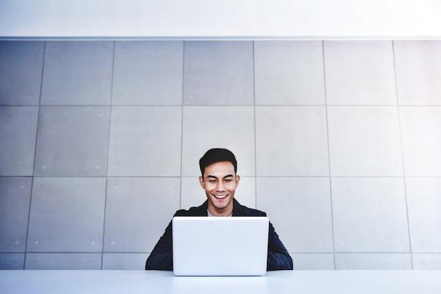 Feliz, jovem, asiático, homem negócios, trabalhando, computador, laptop, em, seu, workplace. sorrindo e olhando para computador portátil