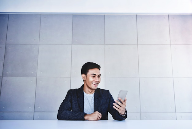 Feliz, jovem, asiático, homem negócios, trabalhando, ligado, smartphone