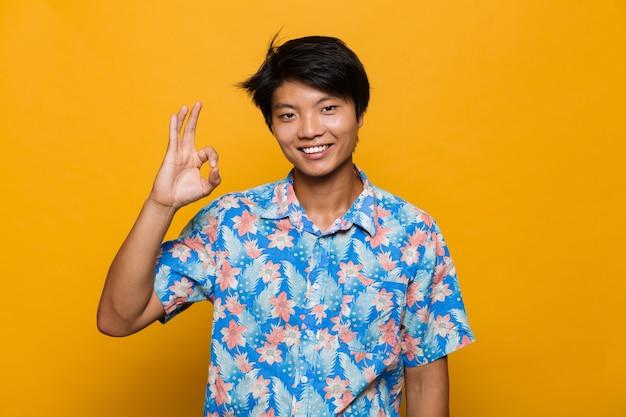 Feliz jovem asiático posando isolado sobre o espaço amarelo, mostrando um gesto certo.
