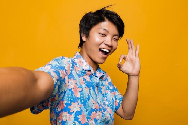 Feliz jovem asiático posando isolado sobre o espaço amarelo, tome uma selfie com um gesto ok.