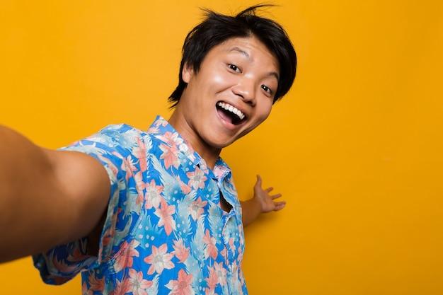 Feliz jovem asiático posando isolado sobre o espaço amarelo, tome uma selfie mostrando copyspace.