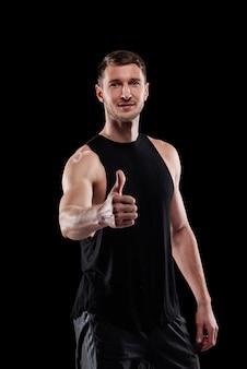 Feliz jovem atleta musculoso de sucesso aparecendo o polegar enquanto posa