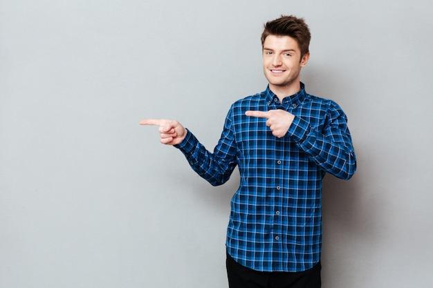 Feliz jovem atraente em cima de parede cinza e apontando
