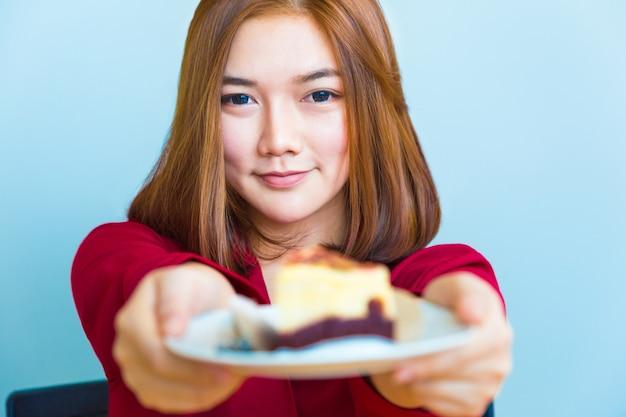 Feliz, jovem, atraente, mulher asian, sorrindo, e, entregando, um, pedaço, de, chocolate, queijo, bolo