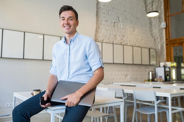 Feliz jovem atraente sorridente homem sentado em um escritório aberto, segurando um laptop,