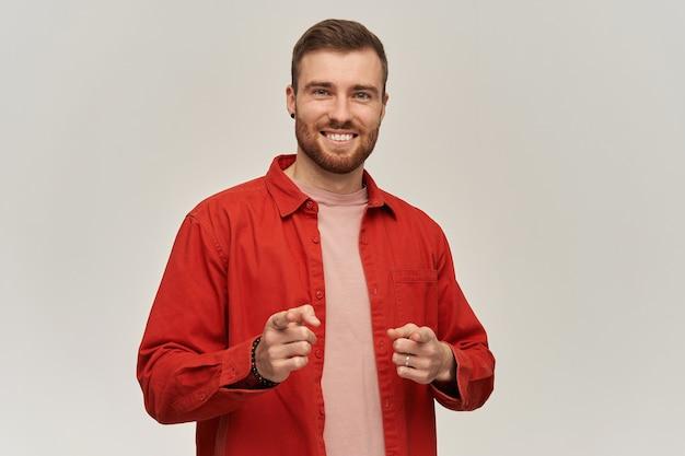 Feliz jovem barbudo atraente de camisa vermelha parece confiante, sorrindo e apontando para você na frente, sobre uma parede branca