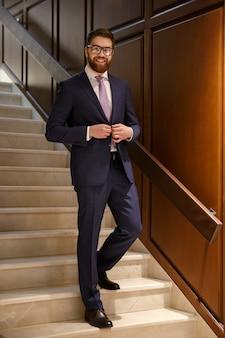 Feliz jovem barbudo empresário em pé na escada
