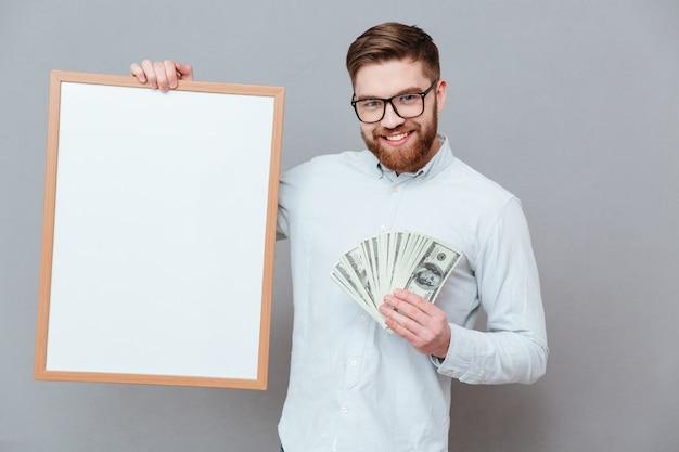 Feliz jovem barbudo empresário segurando copyspace placa e dinheiro