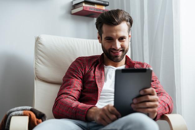 Feliz jovem barbudo usando computador tablet.