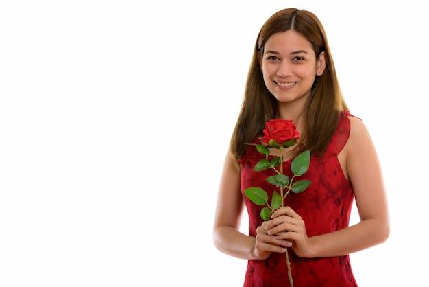 Feliz jovem bonita sorrindo e segurando uma rosa vermelha