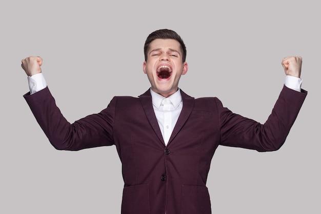 Feliz jovem bonito em um terno violeta e camisa branca, em pé com uma cara de espanto e surpresa, levantou os braços e comemorou sua vitória e gritando. tiro de estúdio interno, isolado em fundo cinza.