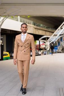 Feliz jovem bonito empresário africano andando pelas ruas da cidade