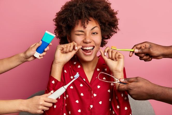 Feliz jovem cacheada escova os dentes com fio dental, se preocupa com a higiene oral, rodeada de pasta de dente, escova de dente elétrica e limpador de língua