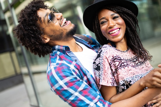 Feliz jovem casal africano abraçando e rindo ao ar livre.
