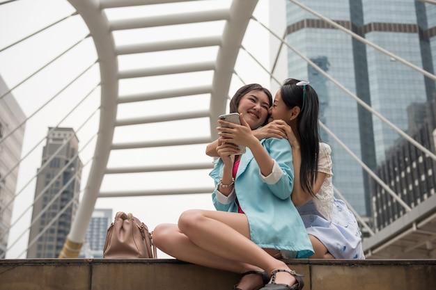 Feliz jovem casal de lésbicas asiáticas abraço e beijo durante o intervalo das compras na cidade urbana. momento doce do mesmo sexo lgbt na cidade.