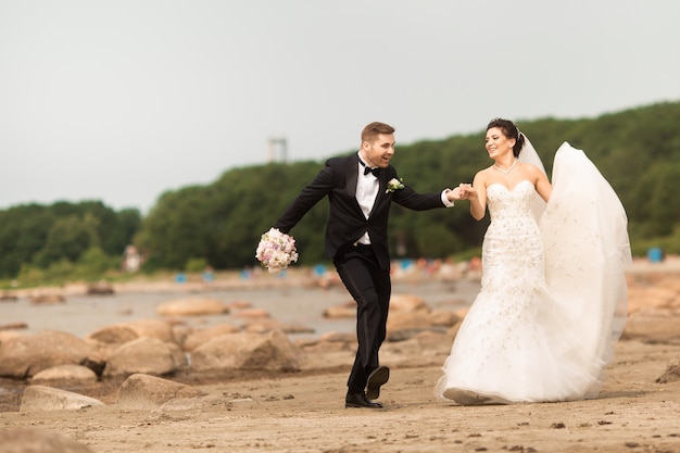 Feliz jovem casal de noivos se divertindo na praia