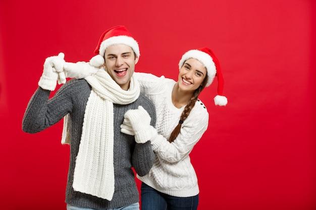 Feliz jovem casal em sweater comemorando o natal com o jogo e a dança.