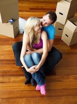 Feliz jovem casal sentado no chão. mudança de casa