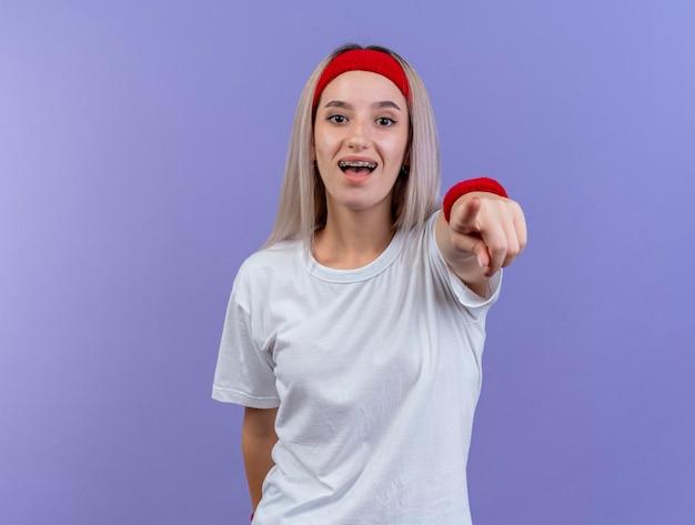 Feliz jovem caucasiana desportiva com aparelho e faixa na cabeça