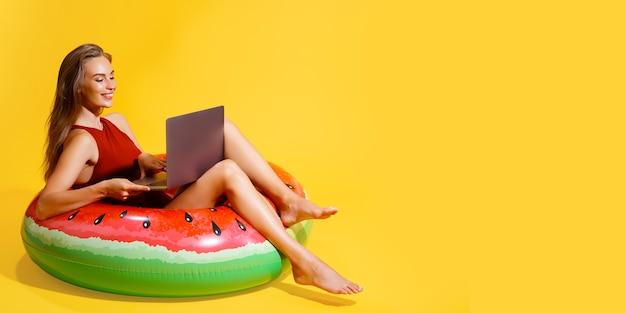 Feliz jovem caucasiana em maiô isolado em fundo amarelo. conceito de resto de férias de verão de pessoas. sente-se no anel inflável de natação, trabalhe no computador laptop.