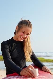 Feliz, jovem caucasiana em traje de banho, tem um sorriso dentuço, encera a prancha de surf, posa contra o céu azul, tem uma expressão satisfeita