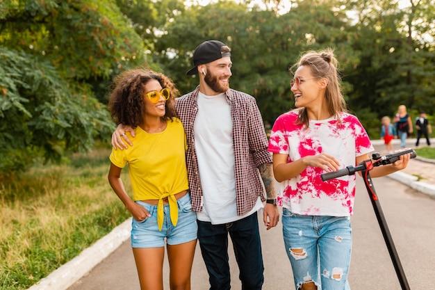 Feliz jovem companhia de amigos sorridentes caminhando no parque com patinete elétrica, homens e mulheres se divertindo juntos