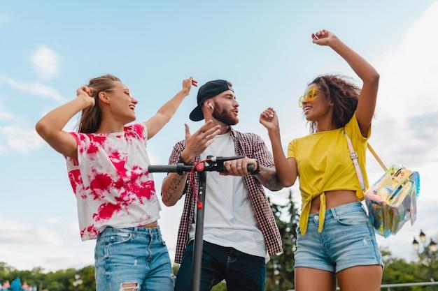 Feliz jovem companhia de amigos sorridentes dançando andando na rua com scooter elétrico, homens e mulheres se divertindo juntos