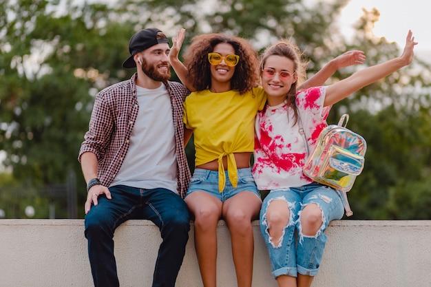 Feliz jovem companhia de amigos sorridentes sentados no parque, homens e mulheres se divertindo juntos