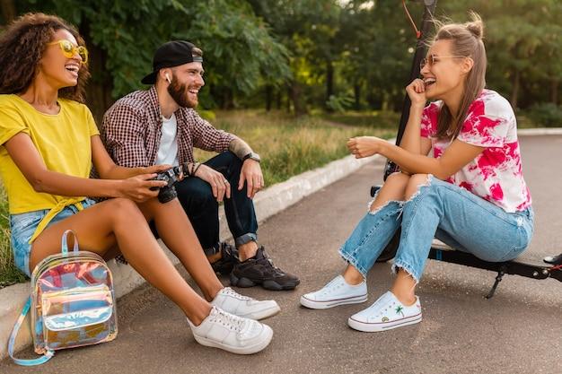 Feliz jovem companhia de amigos sorridentes sentados no parque na grama com patinete elétrica, homens e mulheres se divertindo juntos