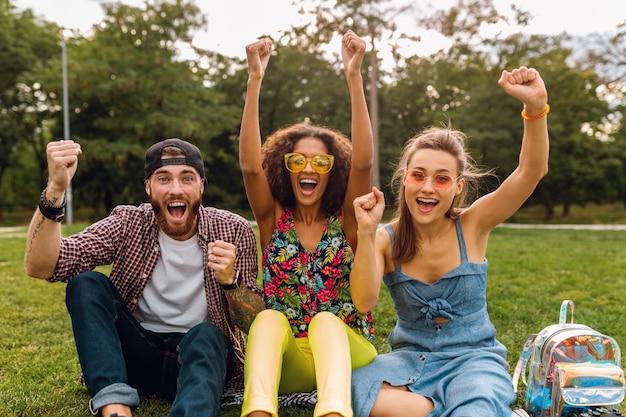 Feliz jovem companhia de amigos sorridentes sentados no parque na grama, homens e mulheres se divertindo juntos