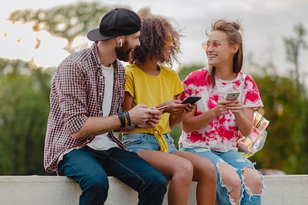 Feliz jovem companhia de amigos sorridentes sentados no parque usando smartphones, homens e mulheres se divertindo