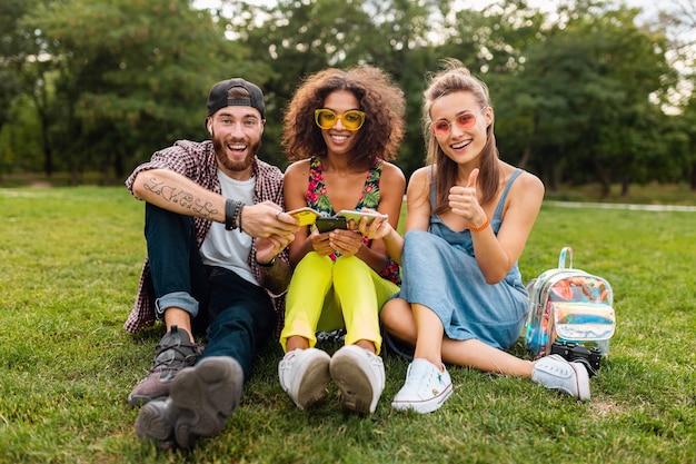 Feliz jovem companhia de amigos sorridentes sentados no parque usando smartphones, se divertindo juntos no estilo colorido de verão, dispositivos de conexão sem fio de comunicação, olhando positivo na câmera