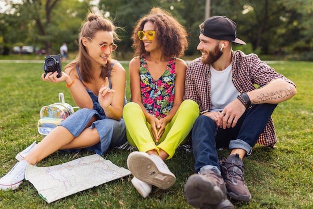 Feliz jovem companhia de amigos sorridentes sentados, sentados no parque, homens e mulheres se divertindo juntos, colorido verão estilo moderno da moda, viajando com a câmera